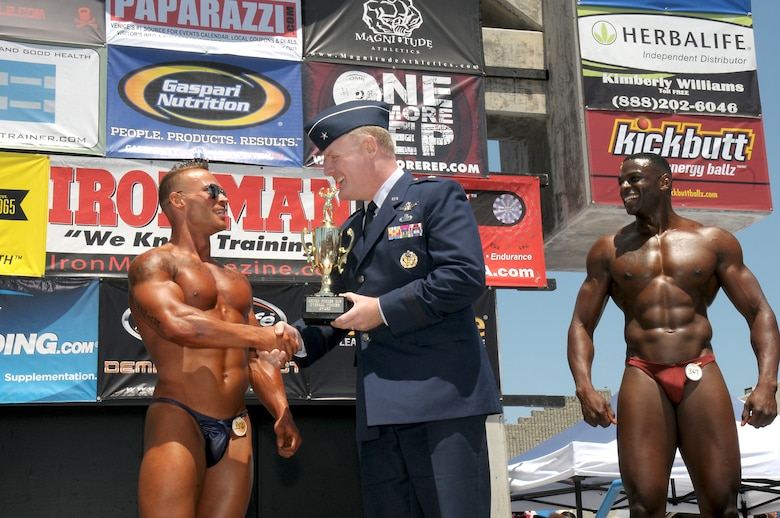 Brigadier Gen. Roger Teague, Space and Missile Systems Center vice commander, presents the Armed Forces Cup to the winner of the military category during the Muscle Beach Classic, May 28. (Photo by Joe Juarez)