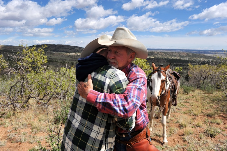 U.S. Army Sgt. Dale Chick (left) is hugged by Andy Popejoy after Chick talked about his experiences in Iraq at the equestrian center April 26, 2012, at the U.S. Air Force Academy in Colorado Springs, Colo. Chick said volunteering at the stables and working with horses helps him find inner peace and comfort after being deployed in Iraq and Afghanistan. Popejoy is an animal caretaker at the center. (U.S. Air Force photo/Val Gempis)