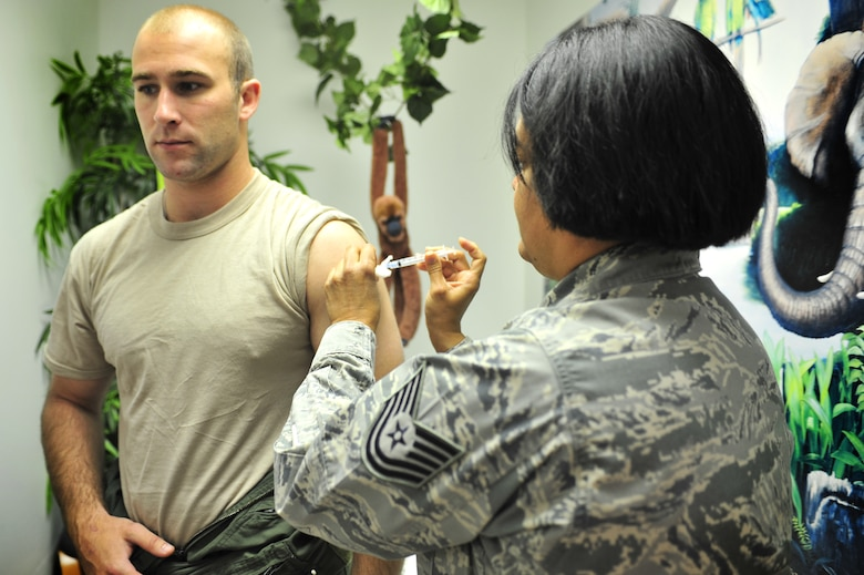 U.S. Air Force Tech. Sgt. Mildred Rosado Canales, 27th Special Operations Support Squadron independent duty medical technician, injects Capt. Buckley Kozlowski, 20th Special Operations Squadron pilot, with a vaccination for Typhoid in the clinic at Cannon Air Force Base, N.M., May 29, 2012. The Typhoid vaccine protects against a type of fever transmitted by ingestion of contaminated food or water. (U.S. Air Force photo by Airman 1st Class Alexxis Pons Abascal)