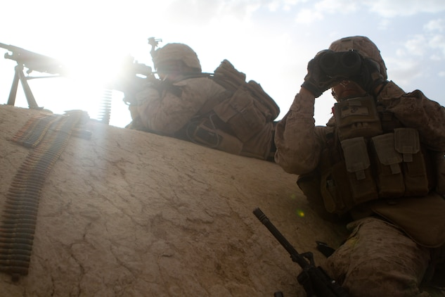 Lance Cpl. Christopher Yudin, a machine gunner with 2nd Battalion, 5th Marine Regiment, works with his spotter, Cpl. Garrett Smith, a team leader with the battalion, during a firefight, May 30, 2012. The Marines eliminated over 50 insurgents with no civilian casualties.