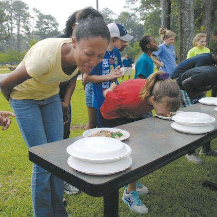 """The last two contestants of the """"Fear Factor"""" event struggle for first place while scarfing down less-than-desirable food. Event coordinators awarded the winner with a $30 gift certificate to the Marine Corps Exchange. Samantha Pappas was the winner and described the food as tasting like """"stale pulled pork."""""""