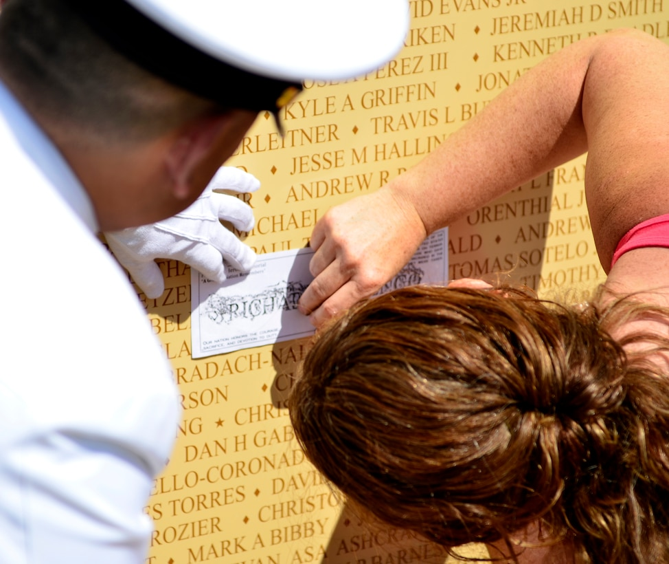 Ret. Navy Chief Petty Officer Carlos Martinez copies a name of a fallen comrade during a Memorial Day ceremony at the Calvary Christian Center, Yuba City, Calif., May 28, 2012. Names of 6,413 Fallen Warriors are listed on 19 panels at the Freedom's Hero Outdoor Memorial. (U.S. Air Force photo by Airman1st Class Ayla Quellhorst/Released)