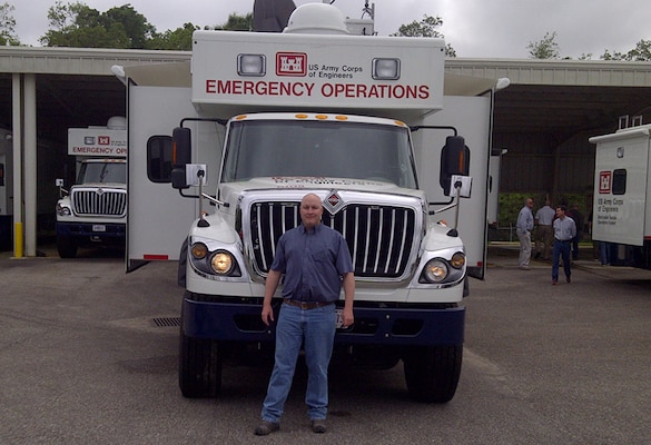Trent Simpler stands in front of one of the Corps' emergency operations response vehicles kept ready for deployment.