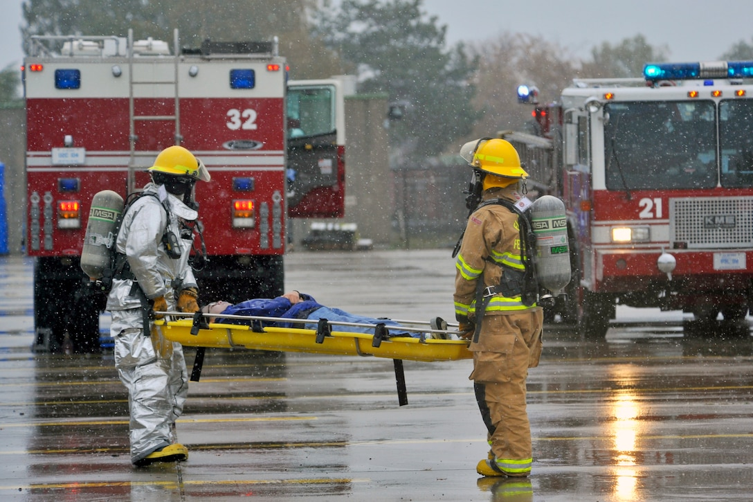 Firefighters with the 886th Civil Engineer Squadron transport a 'victim' during a major accident response exercise, Rhine Ordnance Barracks, Oct. 27. The exercise tested various units' ability to respond to a major accident and their aptitude to work together to handle assorted challenges that may arise during a crisis response. (U.S. Air Force photo/Airman 1st Class Trevor Rhynes)