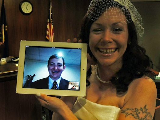 Kari Phelps, spouse of Senior Airman Daniel Phelps, 39th Air Base Wing Public Affairs photojournalist, holds a digital screen of her husband during their online wedding ceremony Oct. 29, 2012, at the Johnson County courthouse in Olathe, Kan. Airman Phelps was unable to attend the actual ceremony, due to being stationed at Turkey, so the couple connected virtually for their special day. (Courtesy photo/Released)