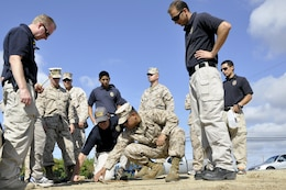 Classmates watch as Jeffery Backus (center), a field training officer here, and Cpl. Anthony Martinez, a patrolman with MP Company, work together to examine footprints during a tracking exercise that is part of a class designed to hone their tracking skills through a new Three-Dimensional Policing Model here Oct. 15-19.