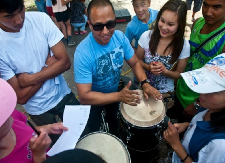 """Senior Airman David Rodriguez plays bongos for Kyrgyz Republic children after a U.S. Air Forces Central Band """"Vector"""" performance at the Mayak Camp. Courtesy photo from AFCENT Band."""