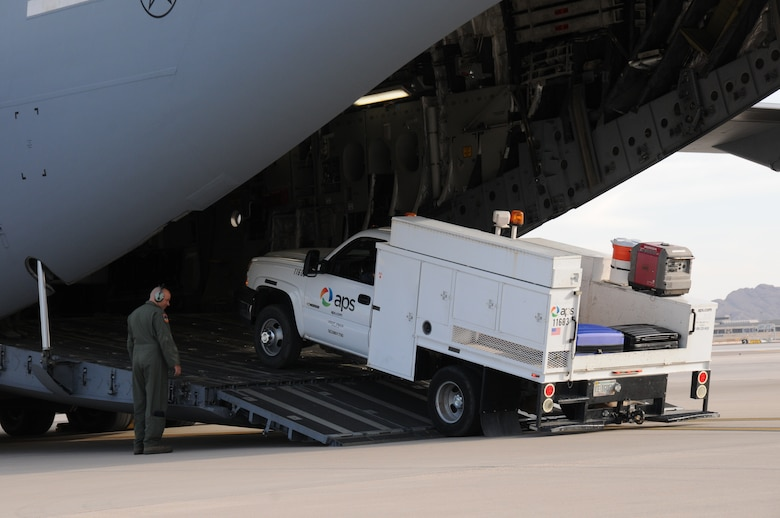 An Air Force loadmaster assigned to 445th Airlift Wing of the Air Force Reserve, load an Arizona Public Service utility vehicle onto a C-17 Globemaster III at the 161st Air Refueling Wing, Phoenix on November 2, 2012.  The 161st ARW will facilitate the loading and transportation of Salt River Project and Arizona Public Service line crews, support staff and required vehicles in efforts to restore power in the aftermath of Hurricane Sandy.   (U.S. Air Force photo by Master Sergeant Kelly Deitloff/Released)