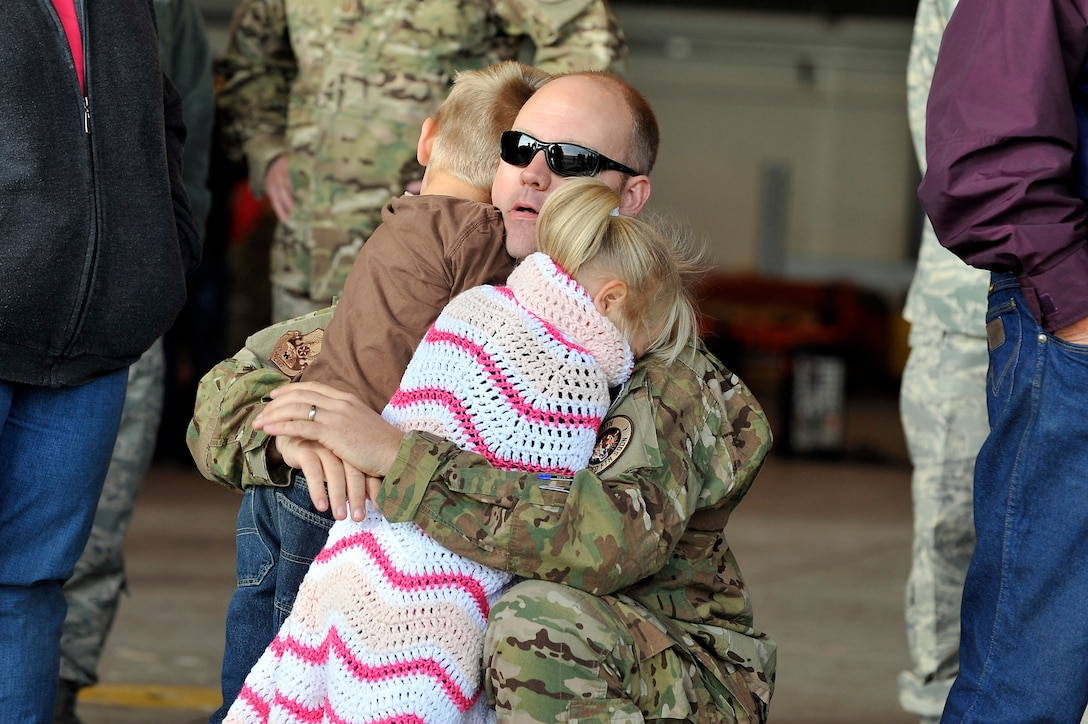 U.S. Air Force Master Sgt. Matthew Morris, 140th Maintenance Squadron, hugs his kids goodbye at Buckley Air Force Base Colo., Nov 1, 2012.  Members of the 140th Wing, Colorado Air National Guard, have been taking off from Buckley AFB, Colo. this week, headed to a forward operating location in support of Air Force Central Command. These pilots, aircraft maintainers and support personnel will be deployed throughout the holiday season in order to support the ongoing Overseas Contingency Operations. (Colorado Air National Guard photo by Tech. Sgt. Wolfram M. Stumpf)