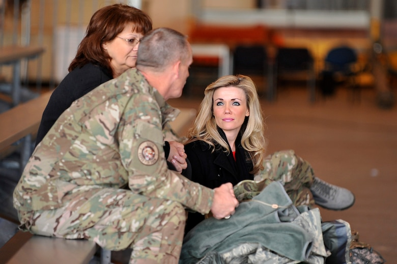 U.S. Air Force Master Sgt. Mark Covalt, 140th Maintenance Squadron, along with his wife LuAnn Covalt (center) and his daughter Gretchen Covalt (right) spend a few moments together before he deploys from Buckley Air Force Base Colo., Nov 1, 2012.  Members of the 140th Wing, Colorado Air National Guard, have been taking off from Buckley AFB, Colo. this week, headed to a forward operating location in support of Air Force Central Command. These pilots, aircraft maintainers and support personnel will be deployed throughout the holiday season in order to support the ongoing Overseas Contingency Operations. (Colorado Air National Guard photo by Tech. Sgt. Wolfram M. Stumpf)