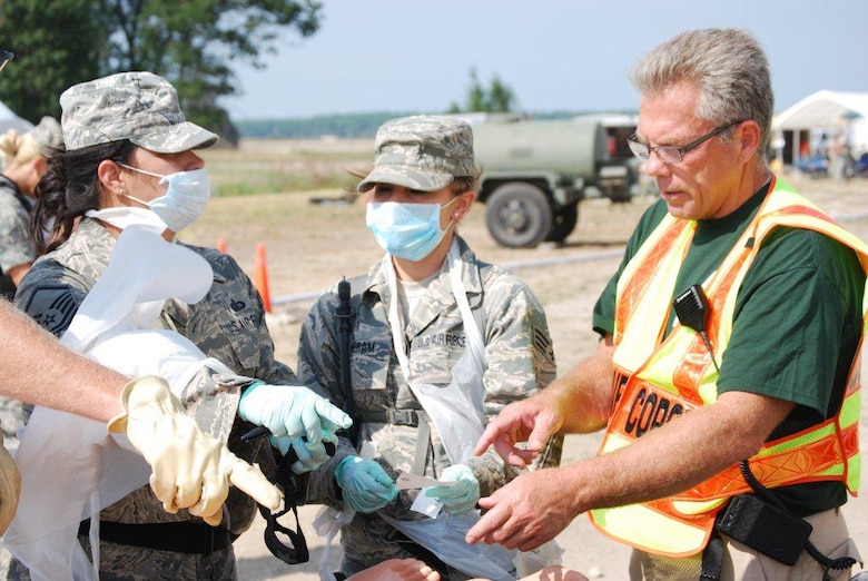 Kentucky Air National Guard Senior Airman Shelby Basham (center), a Fatality Search and Recovery Team member, talks to other FSRT members and the on-scene coroner during Patriot 12, a disaster-response exercise held at Volk Field, Wis., from July 13-20, 2012. The Kentucky Air Guard joined with the Arizona and Minnesota Air Guard FSRTs to train a newly established Indiana team during the exercise. (Courtesy Photo)