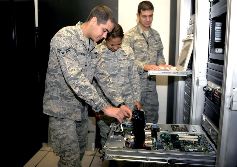 U.S. Air Force Airman 1st Class Steven Iguado, 1st Lt. Liezi-Anne Sarte and Staff Sgt. Robert Kehr, 612th Air Communications Maintenance Squadron, inspect a server on Davis-Monthan Air Force Base, Ariz., Nov. 1, 2012. The shop performs daily inspections on the more than $50 million weapons system. (U.S. Air Force photo by Airman 1st Class Saphfire Cook/Released)