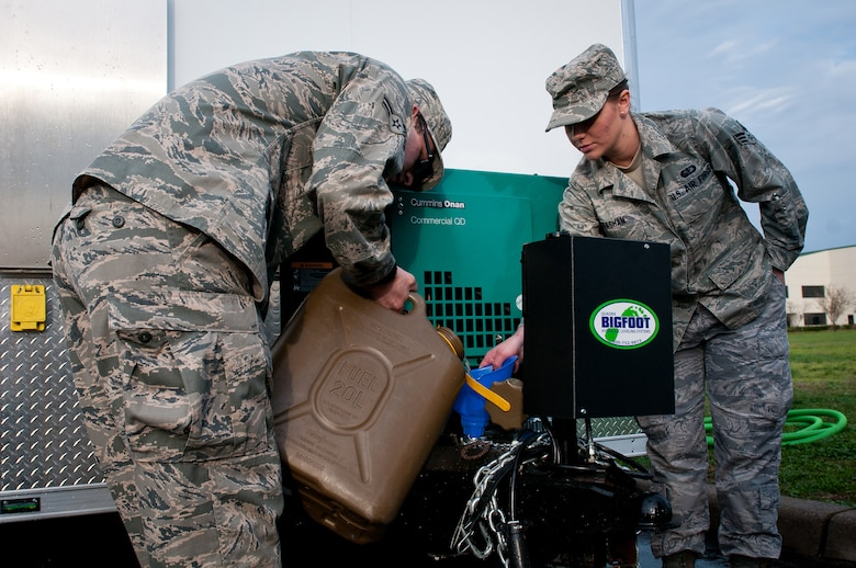 Senior Airman Christian King, left, and Senior Airman Shelby Basham, right, of the 123rd Force Support Squadron fuel a new mobile field kitchen during training at the Kentucky Air National Guard Base in Louisville, Ky., on March 16, 2012. The kitchen can be deployed to the site of a natural disaster to provide hot meals for relief workers. (U.S. Air Force photo by Senior Airman Maxwell Rechel)