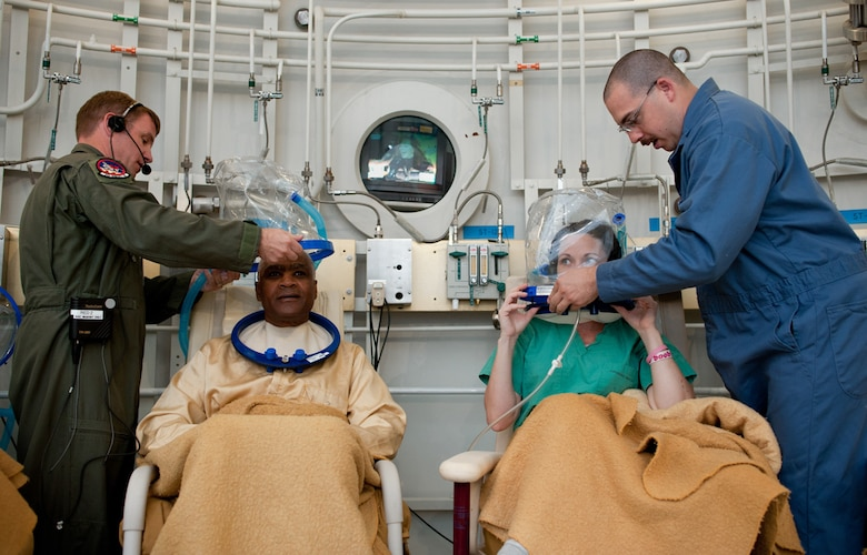 Lt. Col. (Dr.) Michael Richards and Tech. Sgt Christain Simpson help patients attach oxygen-providing hoods prior to a dive in the hyperbaric chamber at David Grant Medical Center. (U.S. Air Force Photo/Ken Wright)