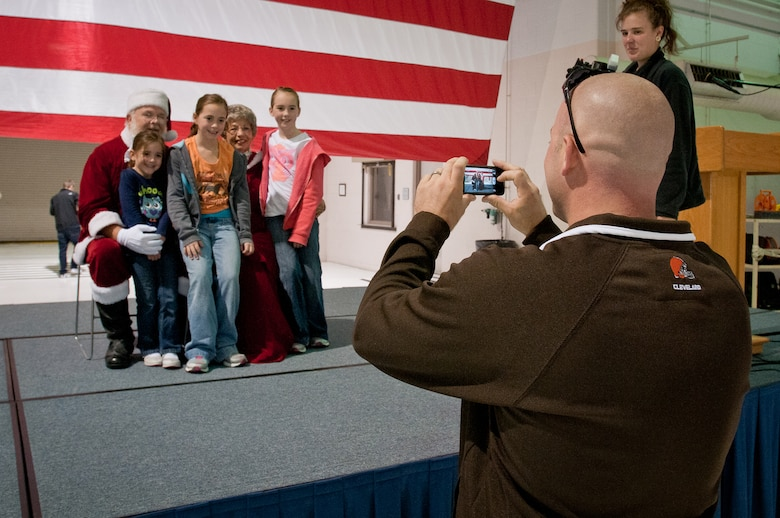 Capt. Jarret Goddard takes a picture of his daughters, Mary-Kate, Madison and Kiersten, during Family Day 2012 at the Kentucky Air Guard Base in Louisville, Ky., on Oct. 21, 2012. Airmen and their family members participated in a range of activities, including ?Christmas in October? and a picnic lunch. (U.S. Air Force photo by Senior Airman Maxwell Rechel)