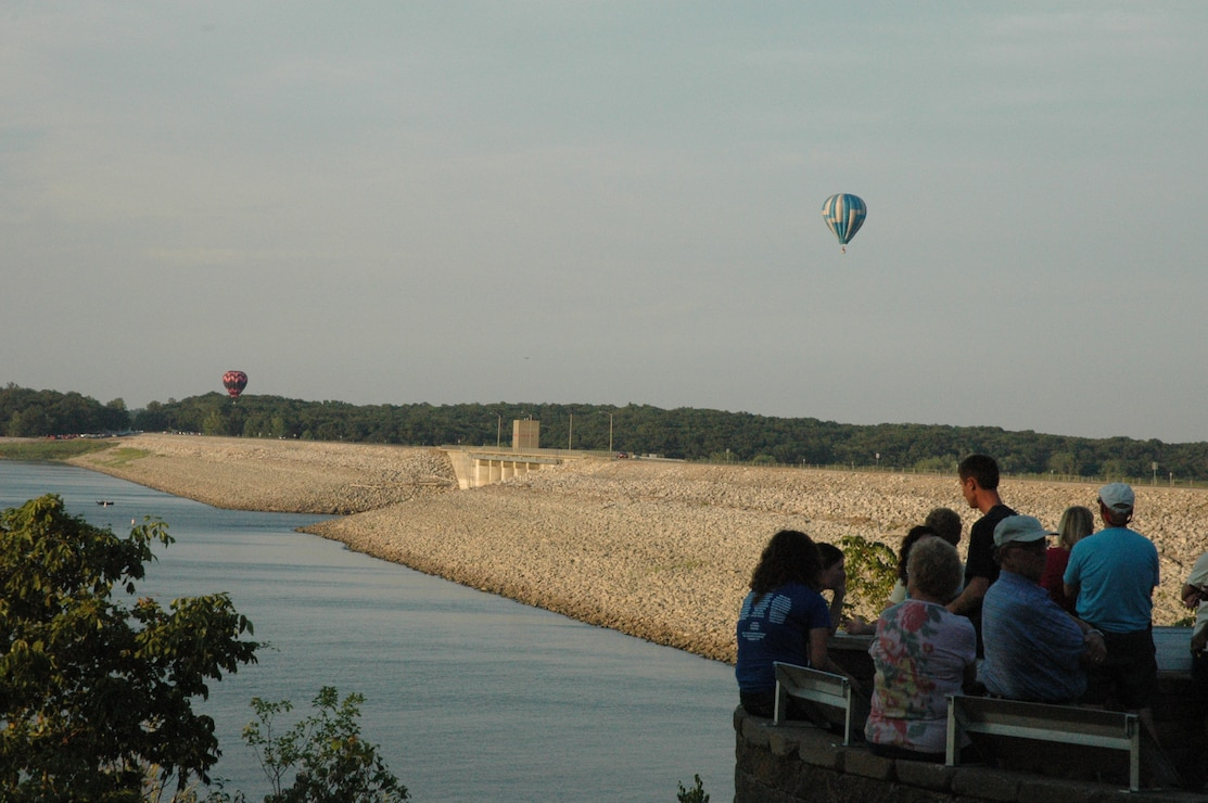 Visitors watch hot air balloons from visitor center patio