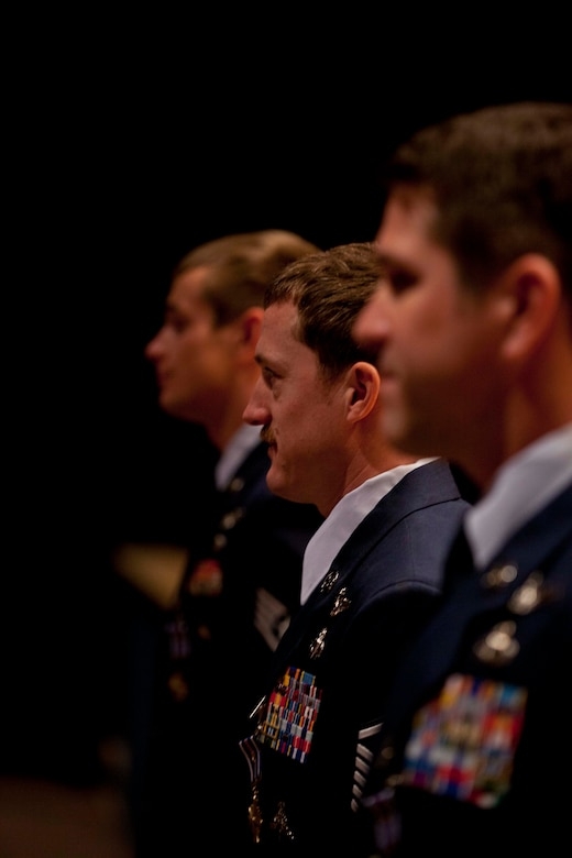 "Master Sgt. Brandon Stuemke (center), Senior Master Sgt. Christopher ""Doug"" Widener (left) and Staff Sgt. Aaron Parcha wait to shake hands with the hundreds of attendees to the Distinguished Flying Cross with Valor Medal presentation at the Talkeetna Theater on Joint Base Elmendorf-Richardson Nov. 3.. The three pararescuemen from the 212th Rescue Squadron conducted more than 20 missions in 5 days, including treating a fellow pararescueman from a gunshot wound while under enemy fire. Photo by Lt. Bernie Kale, Alaska National Guard Public Affairs Office"