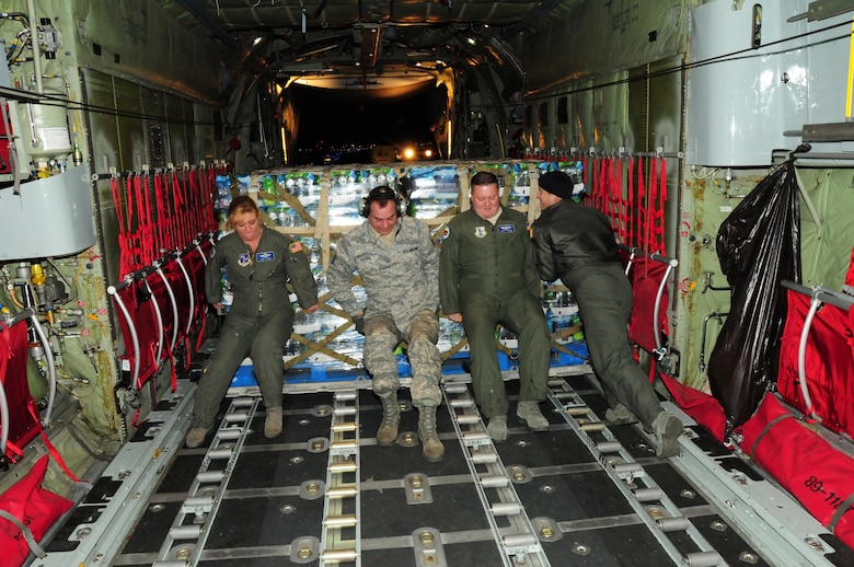 107th Airmen Senior Master Sgt. Terri Santoro, Master Sgt. Vincent Kalota, Tech Sgt. Alan Frankosky and Senior Airman Shaun Pierce use muscle power to push the pallet loaded with water off the aircraft. Nov. 2, 2012 (National Guard Photo/Senior Master Sgt. Ray Lloyd)