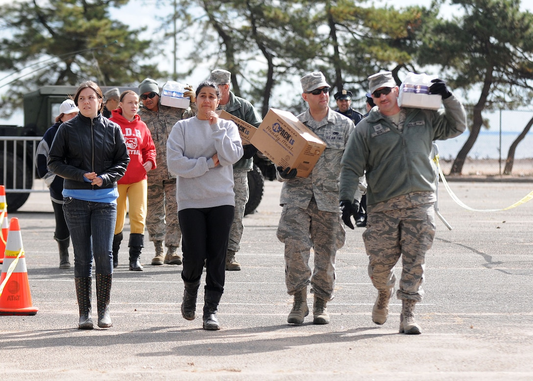Members of the New York Air National Guard's 174th Attack Wing carry food and water for local residences at the Emergency Response location on Staten Island on 2 November 2012.The food and water were provided to people who needed assistance after Hurricane Sandy took down power lines and caused massive destruction to many homes in the area leaving families desperate for help.  (New York Air National Guard photo by Tech. Sgt. Jeremy M. Call/Released)