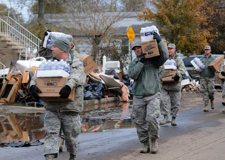 NY Air National Guard Master Sgt. Thomas Moade from the Hancock Field Air National Guard Base, Syracuse, NY leads other members of the 174th as well as members of the New York Army Guard from Newburg in taking water and cases of food to local residents in Staten Island on 2 November 2012. The food and water were provided to people who needed assistance after Hurricane Sandy took down power lines and caused massive destruction to many homes in the area leaving families desperate for help. Moade and the others were taking the food to those who could not make it to the Emergency Response location. (NYANG photo by Tech. Sgt. Jeremy M. Call/Released)