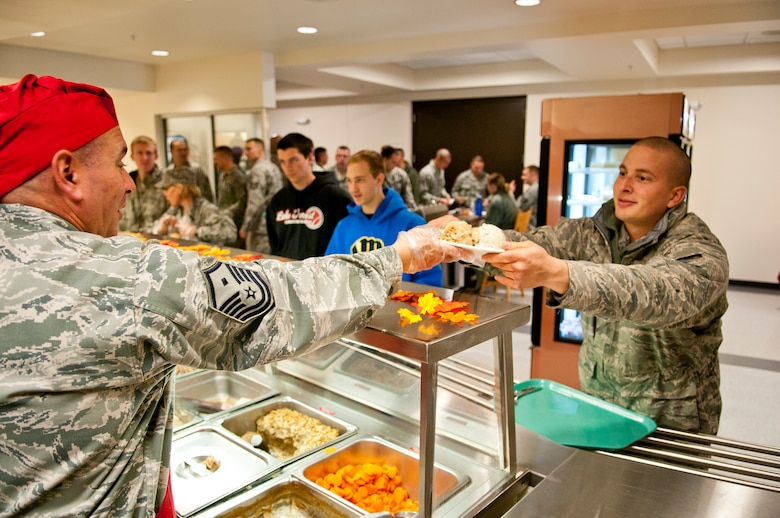 Master Sgt. Michael Harvey, left, first sergeant for the 115th Security Forces squadron, serves Senior Airman Donovan Halajian, crew chief for the 115th Maintenance Group, his holiday meal during the November Unit Training Assembly, at Truax Field, Madison, Wis., Nov. 3, 2012. (U.S. Air Force photo by Tech. Sgt. Ashley Bell)