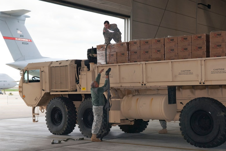 Staff Sgt. Randolph Cutlip hands a strap up to Spc. Craig Brown in a hangar at the 167th Airlift Wing, Martinsburg, W.Va., Nov.2, 2012. The West Virginia National Guardsmen, both assigned to the 77th Brigade's  201st  Forward Support Company, were assisting with storm relief efforts by transporting pallets of water and boxed meals to counties in West Virginia hit hardest by the storm. The 167th AW is serving as a staging area for disaster relief supplies which will then be transported throughout West Virginia as needed. The West Virginia National Guard has over 200 members aiding in recovery efforts from Hurricane Sandy.  The storm blanketed the state with heavy snow and rains and also had severe winds that left homes and properties damaged.  Guardsmen are involved in numerous aspects of the operations from search and rescue missions to debris removal. (Air National Guard photo by Master Sgt. Emily Beightol-Deyerle)