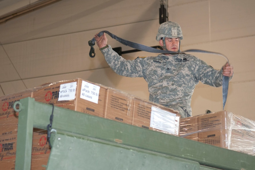 West Virginia National Guardsman, Staff Sgt. Robert Hanna, assigned to the 77th Brigade's 201st Forward Support Company, straps down pallets of boxed ready-to-eat meals on a truck in a hangar at the 167th Airlift Wing, Martinsburg, W.Va., Nov.2, 2012. The truck was destined for Tucker County, W.Va., one of the W.Va. counties with heavy snow and power outages. The 167th AW is serving as a staging area for disaster relief supplies which will then be transported throughout West Virginia as needed. The West Virginia National Guard has over 200 members aiding in recovery efforts from Hurricane Sandy.  The storm blanketed the state with heavy snow and rains and also had severe winds that left homes and properties damaged.  Guardsmen are involved in numerous aspects of the operations from search and rescue missions to debris removal. (Air National Guard photo by Master Sgt. Emily Beightol-Deyerle)