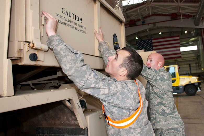 West Virginia National Guardsmen, Spc. Craig Brown, with the 77th Brigade's 201st Forward Support Company and Staff Sgt. John Wishmyer, 167th Airlift Wing, pin down the sides of a truck full of boxed ready-to-eat meals in a hangar at the 167th Airlift Wing, Martinsburg, W.Va., Nov.2, 2012. The truck was destined for Tucker County, W.Va., one of the W.Va. counties with heavy snow and power outages. The 167th AW is serving as a staging area for disaster relief supplies which will then be transported throughout West Virginia as needed. The West Virginia National Guard has over 200 members aiding in recovery efforts from Hurricane Sandy.  The storm blanketed the state with heavy snow and rains and also had severe winds that left homes and properties damaged.  Guardsmen are involved in numerous aspects of the operations from search and rescue missions to debris removal. (Air National Guard photo by Master Sgt. Emily Beightol-Deyerle)