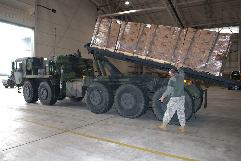 West Virginia National Guardsman, Staff Sgt. Randolph Cutlip, assigned to the 77th Brigade's  201st  Forward Support Company, directs a roll-off with pallets of boxed ready-to-eat meals into place in a aircraft hangar at the 167th Airlift Wing, Martinsburg, W.Va., Nov.2, 2012. The 167th AW is serving as a staging area for disaster relief supplies which will then be transported throughout West Virginia as needed. The West Virginia National Guard has over 200 members aiding in recovery efforts from Hurricane Sandy.  The storm blanketed the state with heavy snow and rains and also had severe winds that left homes and properties damaged.  Guardsmen are involved in numerous aspects of the operations from search and rescue missions to debris removal. (Air National Guard photo by Master Sgt. Emily Beightol-Deyerle)