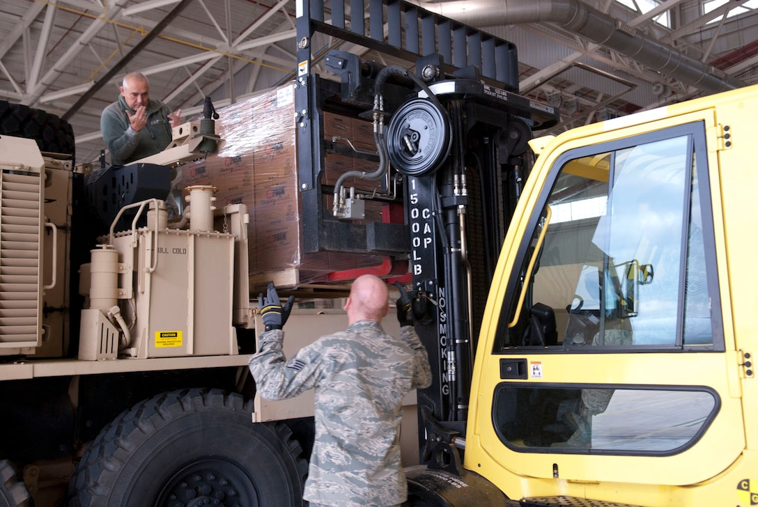 West Virginia National Guardsmen, Staff Sgt. Randolph Cutlip, a truck driver with the 77th Brigade's  201st  Forward Support Company and Staff Sgt. John Wishmyer, 167th Airlift Wing, direct a pallet of ready to eat boxed meals onto a truck at the 167th AW, based in Martinsburg, W.Va., Nov. 2, 2012. The 167th AW is serving as a staging area for disaster relief supplies which will then be transported throughout West Virginia as needed. The West Virginia National Guard has over 200 members aiding in recovery efforts from Hurricane Sandy.  The storm blanketed the state with heavy snow and rains and also had severe winds that left homes and properties damaged.  Guardsmen are involved in numerous aspects of the operations from search and rescue missions to debris removal. (Air National Guard photo by Master Sgt. Emily Beightol-Deyerle)