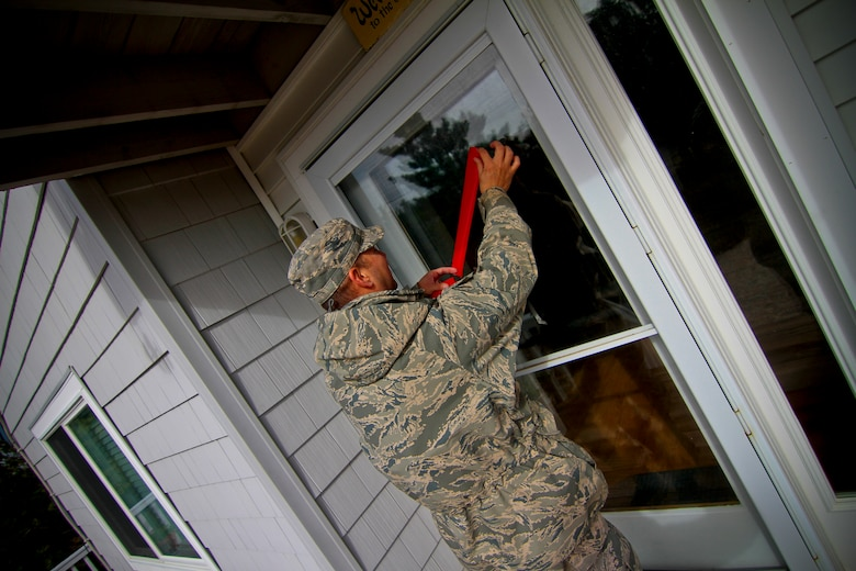 A picture of an Airmen from the 177th Fighter Wing placing red tape over a glass door.