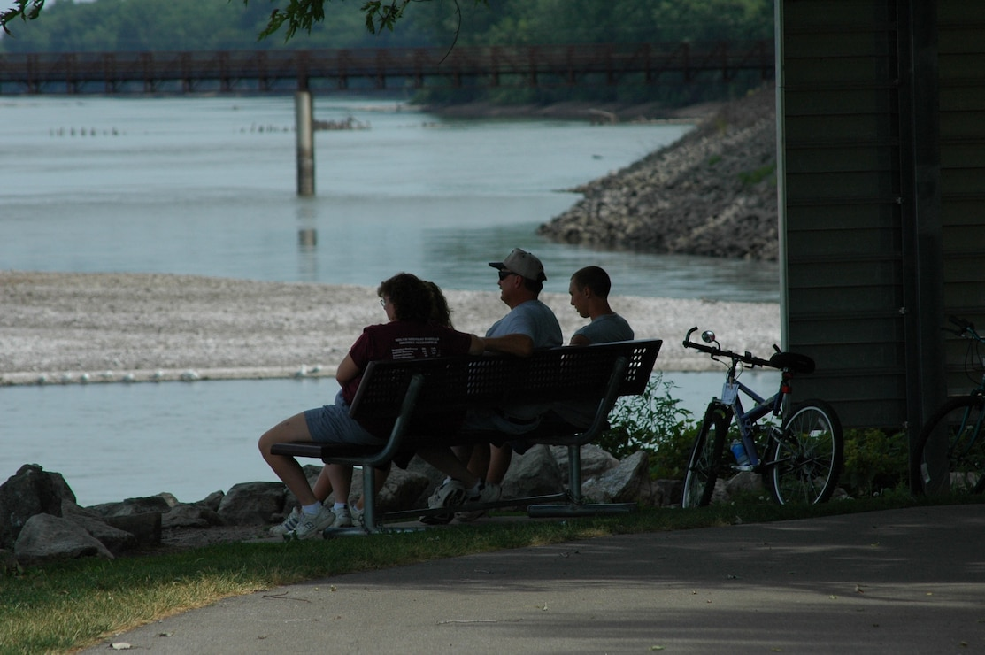 Family sitting on bench watching river in South Tailwater