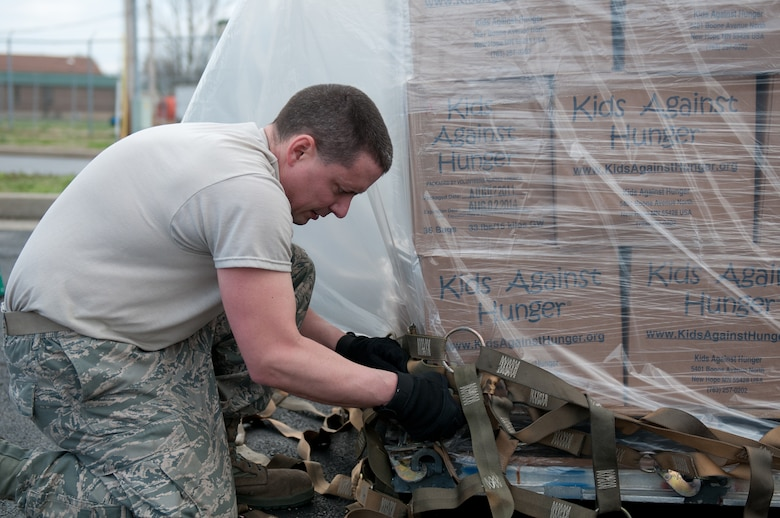 Staff Sgt. Raymond Graves III, an air cargo specialist with the 123rd Logistics Readiness Squadron, secures cargo netting on a pallet of humanitarian goods bound for Haiti on March 13, 2012. The Kentucky Air National Guard is helping Children???s Lifeline, a Kentucky-based non-profit organization, ship food and other supplies to Haiti through the Denton Program. The Denton Program is a U.S. government effort that allows private citizens and organizations to use space available on U.S. military cargo planes to transport humanitarian goods. (U.S. Air Force photo by Master Sgt. Phil Speck)