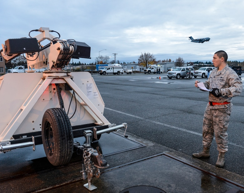 Airman 1st Class Joseph Flores-Constancio, 62nd Aerial Port Squadron cargo processing journeyman, weighs a portable light cart belonging to Bonneville Power Administration, Nov. 3, 2012, as a C-17 Globemaster III aircraft flies overhead, at Joint Base Lewis-McChord, Wash. Before being transported on an aircraft, cargo must be weighed and measured to ensure the aircraft is balanced in flight. (U.S. Air Force photo/Staff Sgt. Sean Tobin)