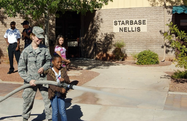 NELLIS AIR FORCE BASE, Nev. -- (Front left) Airman First Class Marissa Henderson, 99th Civil Engineer Squadron Fire Protection Flight, shows a student from Lowman Elementary School how to spray a fire here hose Nov. 5. The exhibition was part of a graduation ceremony for the STARBASE Nellis class. STARBASE is a science, technology, engineering and math-focused program geared toward fifth grade students in the Las Vegas Valley. At the completion of the five-day instruction, Airmen from the base demonstrate their job skills to orient the students with different career options. (U.S. Air Force photo/Myles Judd)