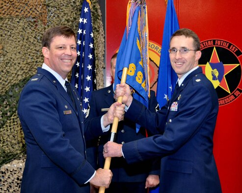 SCHRIEVER AIR FORCE BASE, Colo. -- (Right) Lt. Col. Daniel Bourque, 26th Space Aggressor Squadron, receives the guideon from Col. John Breeden, 926th Group commander, during his assumption of command ceremony at the Space Aggressor Warehouse on Nov. 3. (U.S. Air Force photo/Dan Santistevan)