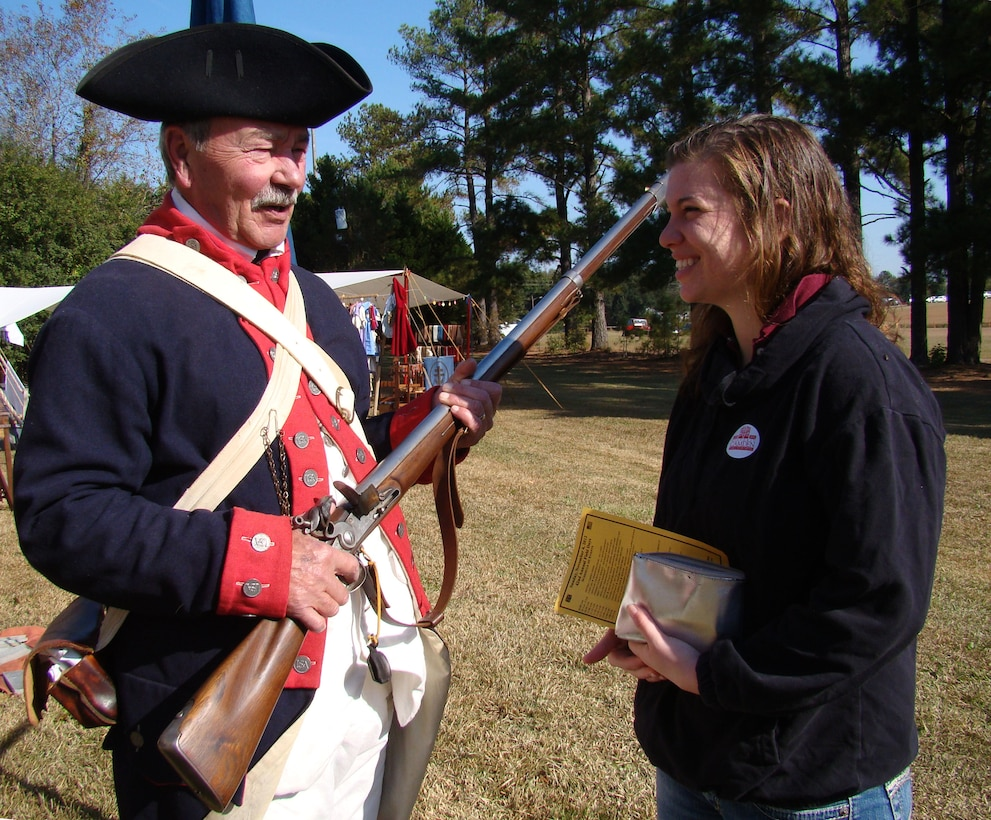 Buddy Bell, who portrays a rebel soldier of the American Revolution, explains his antique rifle to Airman Jodi Lange, 20th Medical Group pharmacy technician, at the Battle of Camden re-enactment Nov. 3, 2012, Camden, S.C. More than 200 actors, including many military veterans, brought the battlefield back to life 232 years after the event. (U.S. Air Force photo by Rob Sexton/Released)