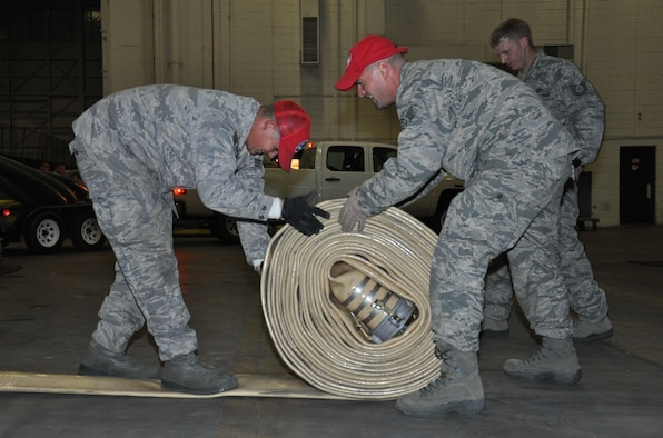 Staff Sgt. John Johnson and Senior Airman Jerl Dunn, of the 823rd Red Horse Squadron, from Hurlburt Field, Fla., role a low-pressure hose and before loading it onto a trailer while staged at Joint Base McGuire-Dix-Lakehurst, N.J., Nov. 4, 2012, to prepare for hurricane relief operations. Approximately 50 Air Force civil engineers and 12 industrial pumps were sent from different locations around the country to form the 331st Air Expeditionary Group, whose mission is to help clear flood water from critical areas damaged by Hurricane Sandy.  (U.S. Air Force photo by Capt. Sybil Taunton/Released)
