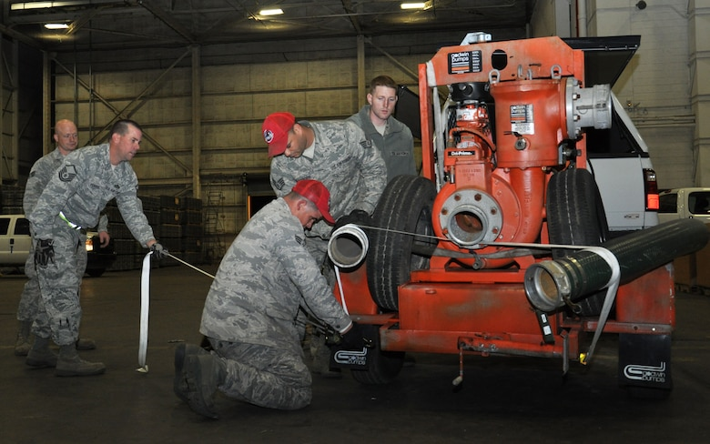 Members of the 331st Air Expeditionary Group strap down pump equipment while staged at Joint Base McGuire-Dix-Lakehurst, N.J., Nov. 4, 2012, and prepare for movement to Fort Hamilton, N.Y., in support of hurricane relief efforts. The 331st AEG is made up of nearly 50 Air Force civil engineers from various duty locations across the country, and 12 industrial pumps that will help clear flood water from critical areas damaged by Hurricane Sandy. (U.S. Air Force photo by Capt. Sybil Taunton/Released)
