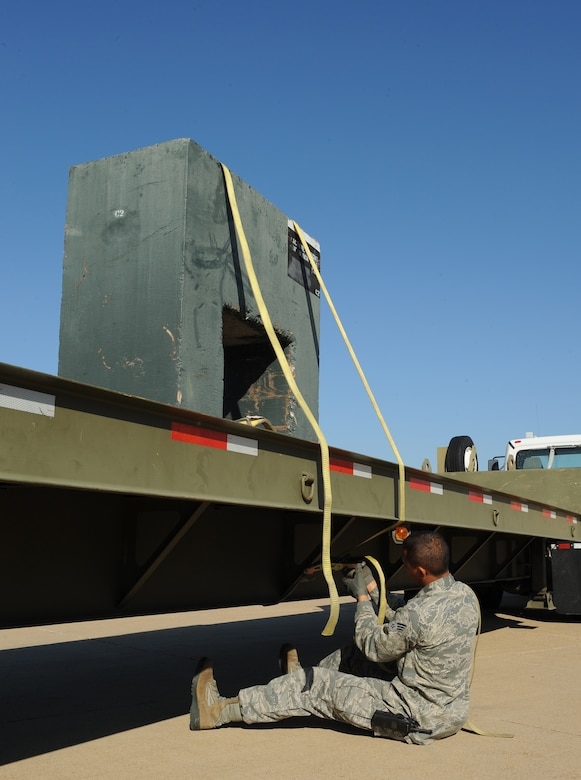 Senior Airman Pierre Brown, 2nd Logistics Readiness Squadron Vehicle Operations journeyman, ensures one side of a training block is tied down to a 45 foot trailer during a training scenario on Barksdale Air Force Base, La., Oct. 31. Vehicle operators support the Barksdale mission by driving aircrew to and from their aircraft as well as delivering parts to maintainers on the flightline. (U.S. Air Force photo/Airman 1st Class Benjamin Gonsier)(RELEASED)