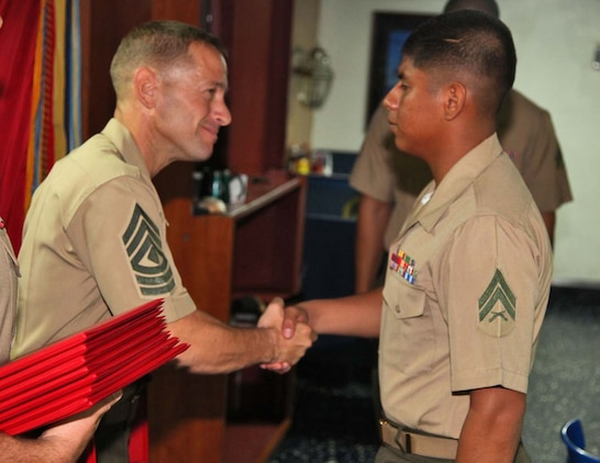 Corporal Edgar Carachure, artillery cannoneer, 1st Platoon, Battery B, Battalion Landing Team 3/5, 15th Marine Expeditionary Unit, shakes hands with 1st Sgt. Yomen J. English, 1st Sgt., Weapons Company, BLT 3/5, 15th MEU, during the graduation ceremony for a Corporals course aboard the USS Rushmore, Nov. 2. The Marines devoted 81 hours to physical training, lectures, practical application, performance evaluations, written evaluations and counselings during the course. The 15th MEU is deployed as part of the Peleliu Amphibious Ready Group as a theater reserve and crisis response.