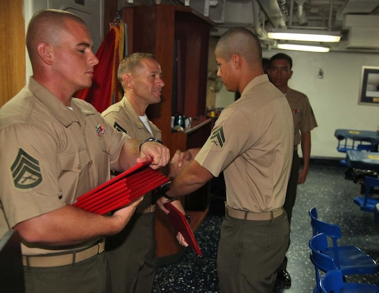 Corporal Andres Chavarin, field wireman, 2nd Platoon, Battery B, Battalion Landing Team 3/5, 15th Marine Expeditionary Unit, shakes hands with 1st Sgt. Yomen J. English, 1st Sgt., Weapons Company, BLT 3/5, 15th MEU, during the graduation ceremony for a Corporals course aboard the USS Rushmore, Nov. 2. The Marines devoted 81 hours to physical training, lectures, practical application, performance evaluations, written evaluations and counselings during the course. The 15th MEU is deployed as part of the Peleliu Amphibious Ready Group as a theater reserve and crisis response.
