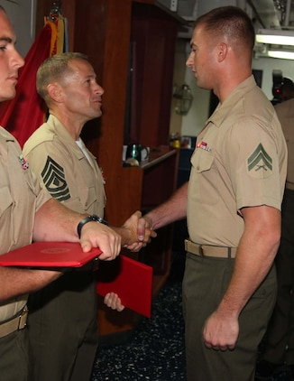 Corporal Joshua Plachy, military policeman, Military Police Detachment, Combat Logistics Battalion 15, 15th Marine Expeditionary Unit, shakes hands with 1st Sgt. Yomen J. English, 1st Sgt., Weapons Company, Battalion Landing Team 3/5, 15th MEU, during the graduation ceremony for a Corporals course aboard the USS Rushmore, Nov. 2. The Marines devoted 81 hours to physical training, lectures, practical application, performance evaluations, written evaluations and counselings during the course. The 15th MEU is deployed as part of the Peleliu Amphibious Ready Group as a theater reserve and crisis response.