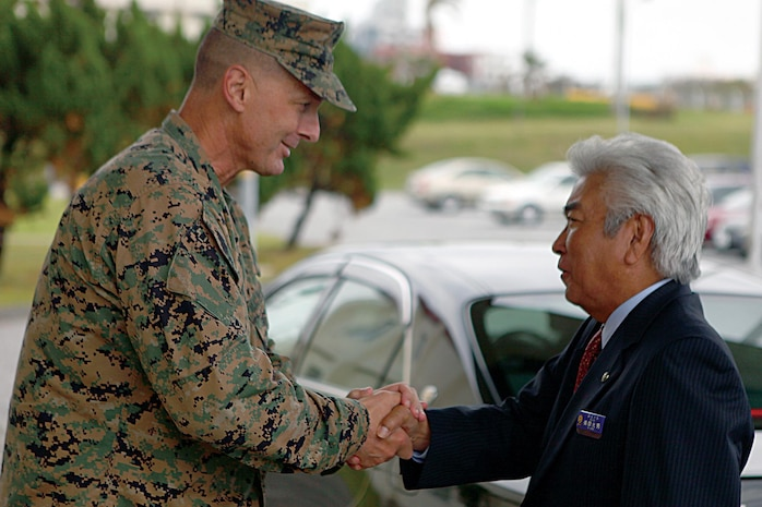 Col. John E. Kasperski welcomes Urasoe City Mayor Mitsuo Gima aboard Camp Kinser during a tour of the camp Nov. 5. Kasperski is the Camp Kinser camp commander and the commanding officer of Combat Logistics Regiment 37, 3rd Marine Logistics Group, III Marine Expeditionary Force.