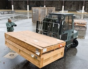 Members of the 436th Logistics Readiness Squadron reposition supply assets to outside covered storage facilities Oct. 30, 2012, at Dover Air Force Base, Del. Assets normally stored outside were brought in prior to Hurricane Sandy's arrival. (U.S. Air Force photo/Roland Balik)