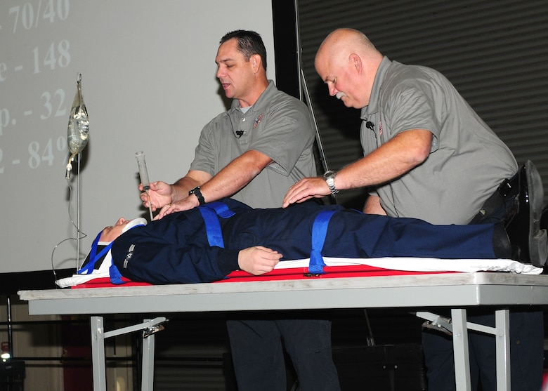 Scott Neusch (left) and Greg McCarty (right) both Fla. fire department paramedics demonstrate how to relieve a collapsed lung on Airman 1st Class Zachary Lessley, 9th Communication Squadron knowledge operations manager. The demonstration showed steps needed to stabilize a victim. (U.S. Air Force photo by Senior Airman Allen Pollard)