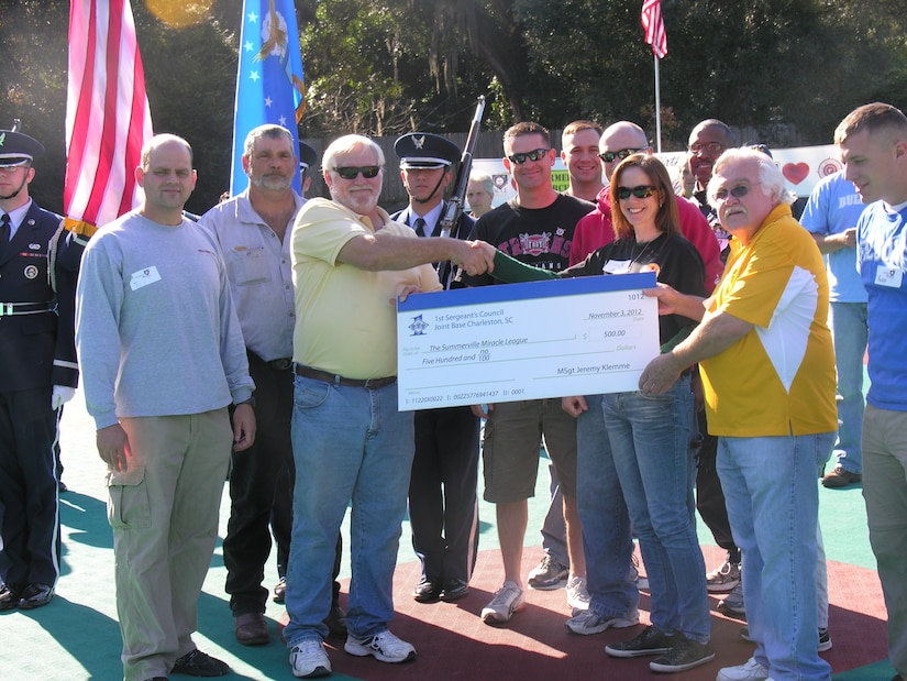 Lt. Col. White 437th Maintenance Squadron commander and Master Sgt. Jennifer Crerar, 16th Airlift Squadron first sergeant (center) present a check for $500 to members of the Summerville Miracle League Nov. 2, 2012, in Summerville, S.C. (U.S. Air Force photo/ Senior Airman Adrian Welch)