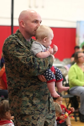 Gunnery Sgt. Justin Cooke, an air traffic controller with Headquarters and Headquarters Squadron, holds his son, Steel, for a better view of The Sesame Street/ USO Experience for Military Families at Marine Corps Air Station Beaufort's fitness center, Nov. 6. The exclusive live performance feautured characters from Sesame Street to help children relate and cope with the challenges that coincide military lifestyle.