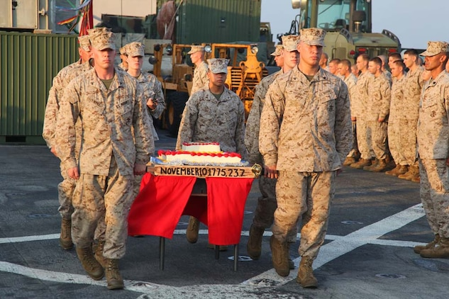 Marines from the 15th Marine Expeditionary Unit carry the ceremonial birthday cake during an early Marine Corps Birthday celebration on the flight deck of the USS Rushmore, Nov. 7. The 15th MEU is deployed as part of the Peleliu Amphibious Ready Group as a theater reserve and crisis response force throughout U.S. Central Command and the U.S. 5th Fleet area of responsibility.