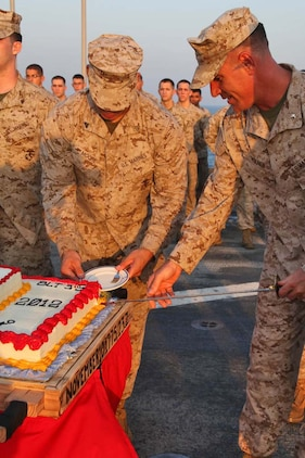 Lieutenant Col. John J. Wiener, commanding officer, Combat Logistics Battalion 15, 15th Marine Expeditionary Unit, slices a piece of cake during an early Marine Corps Birthday celebration on the flight deck of the USS Rushmore, Nov. 7. The 15th MEU is deployed as part of the Peleliu Amphibious Ready Group as a theater reserve and crisis response force throughout U.S. Central Command and the U.S. 5th Fleet area of responsibility.